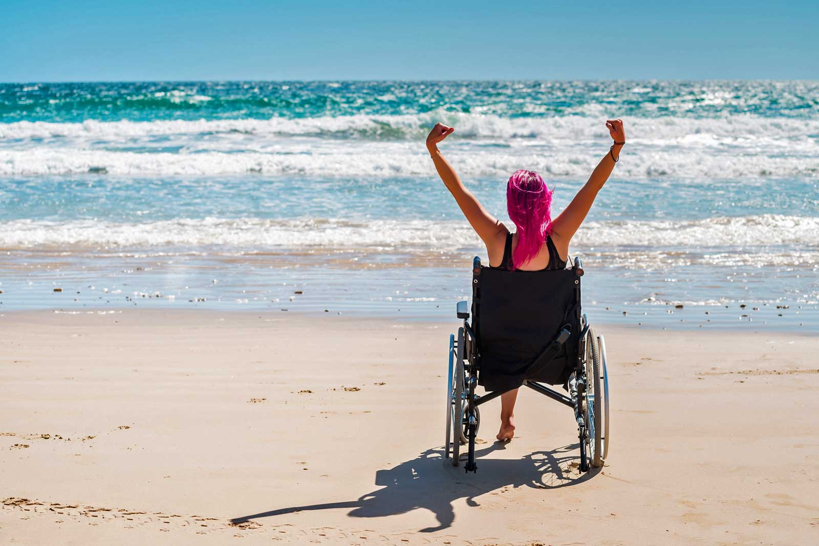Happy girl on a wheelchair on the beach